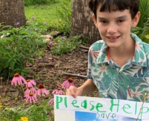 A boy, Brice Claypoole, shows a poster he made about saving Orange Hammock Ranch.