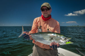 Man holds a bonito, a type of tuna.